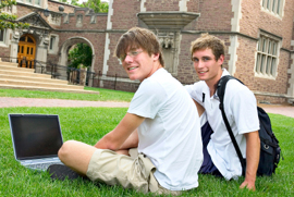 Two young men sitting on the DE campus lawn just after class